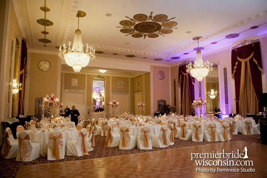 Beautiful Wedding Reception Ballroom with covers chairs with gold accents.