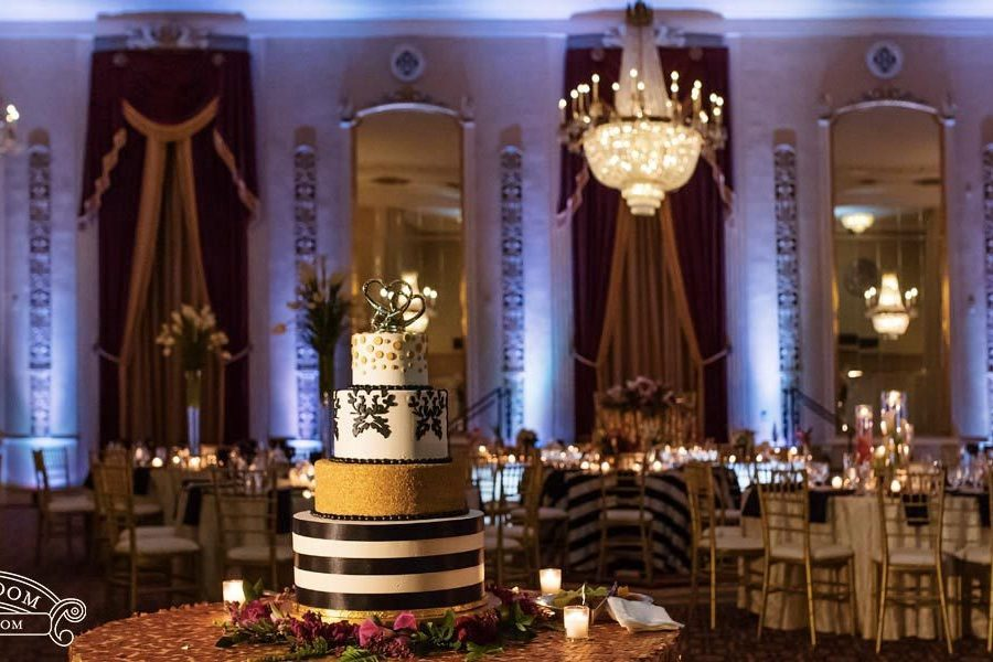 Ballroom in background with gorgeous black, cream and gold color wedding cake