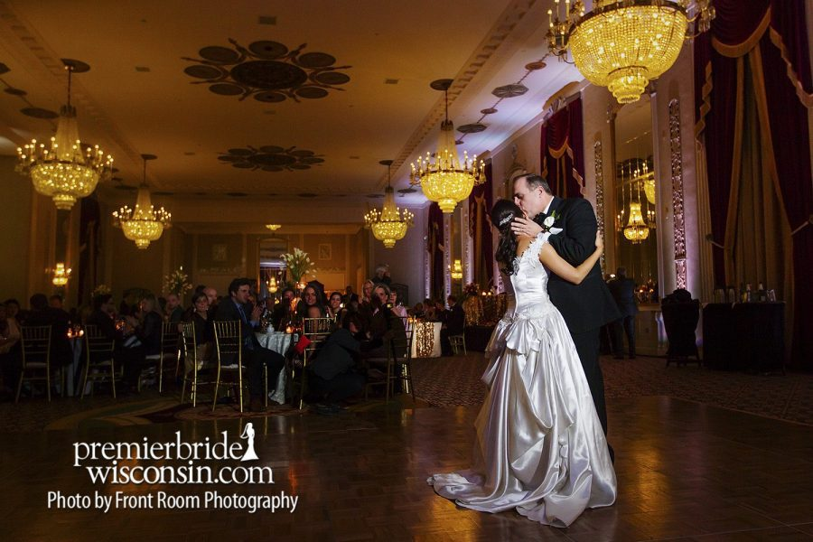 Wedding couple dancing in forefront of decorated ballroom