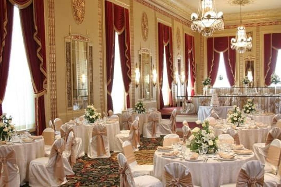 Fully decorated wedding reception with white and green centerpieces, chair covers with gold ties.