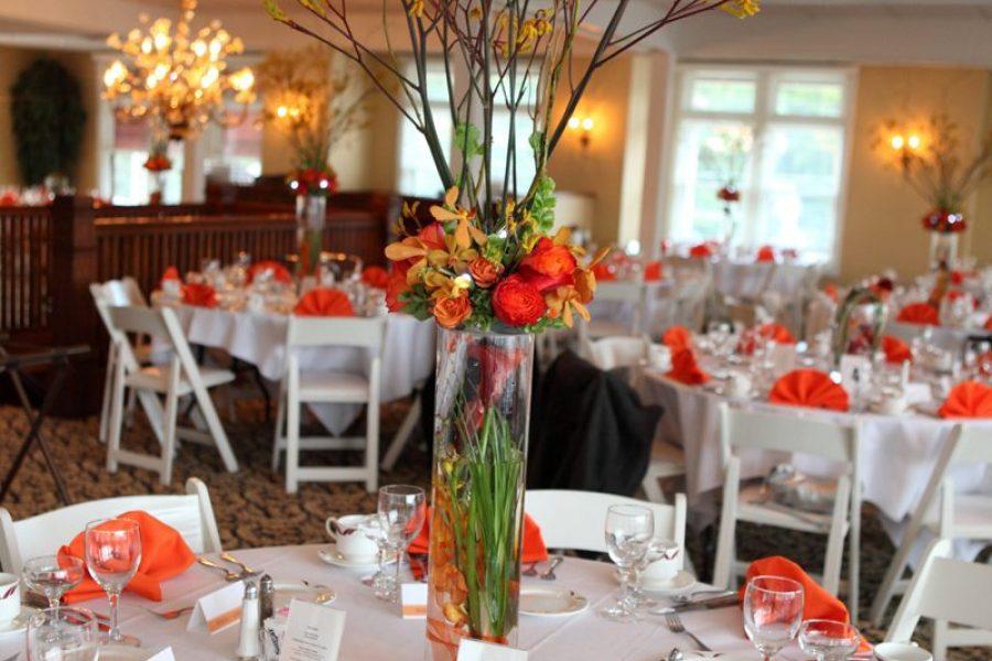 Elegant wedding reception with white linens and orange floral arrangements and napkins
