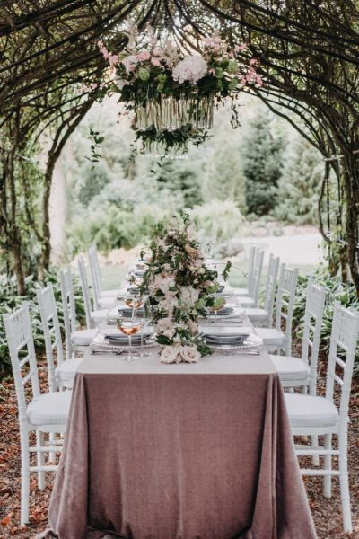 Beautiful garden table-scape set under archway- Rentals by Well Dressed Tables