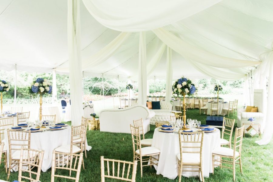 Elegant tented wedding reception with chiavari chairs and round tables with white linens