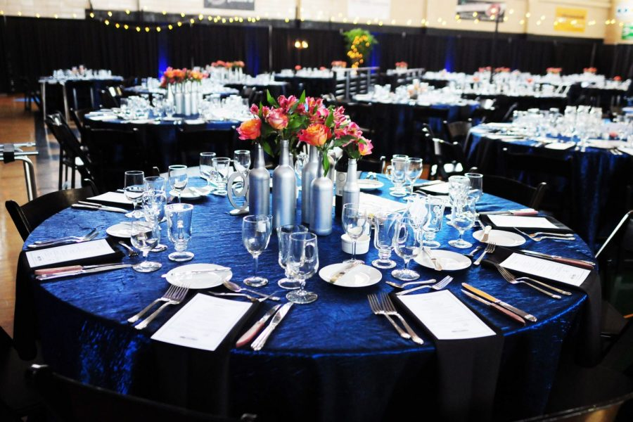 Table-scape with dark blue tablecloth and multiple vase centerpiece. Rentals by Well Dressed Tables