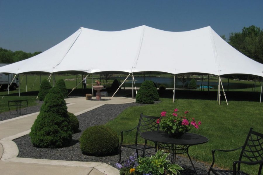 Large white tension tent on green lawn by Celebrations Tent & Party Rentals