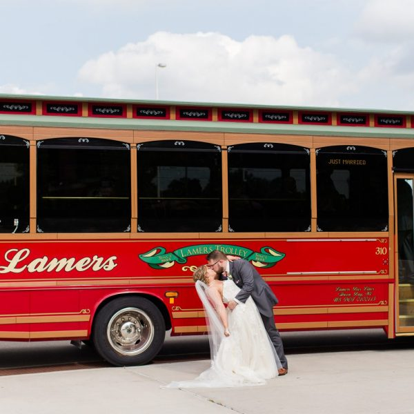 Bride and Groom kissing in front of trolley for their wedding day