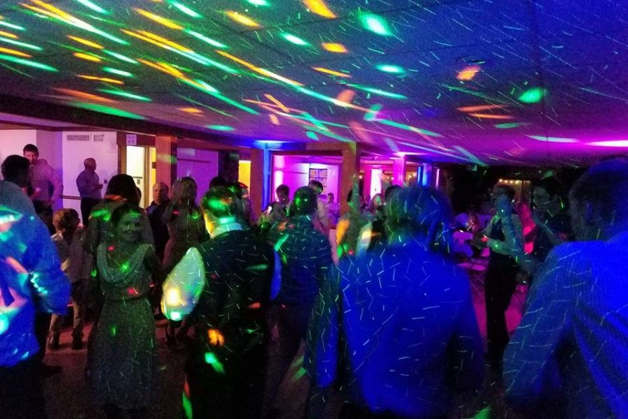 wedding dance floor with guest dancing and colorful lighting effects.