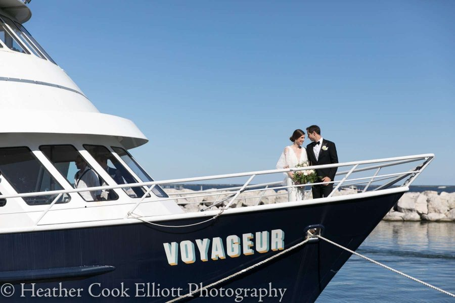 Bride and groom at front of yacht in intimate pose