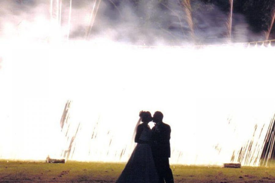 ground fireworks display with black silhouette of wedding couple in forefront