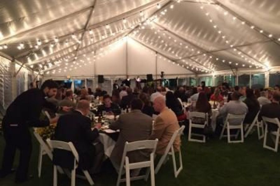 Wedding guests dinning on catering provided by Davians under a lighted tent