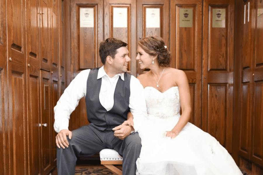 Cute pose of wedding couple looking at each other sitting inside West Bend Country Club