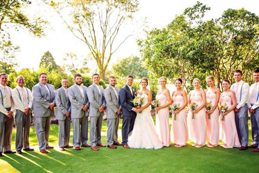 Wedding couple with wedding party dressed in grays and light pink on country club grounds