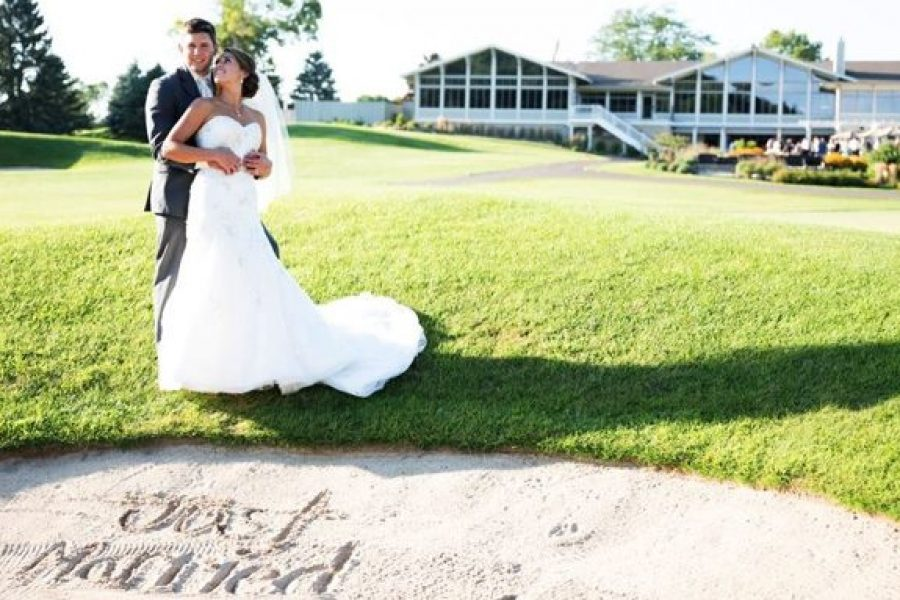 Cute pose of couple on golf course with Country Club building in background