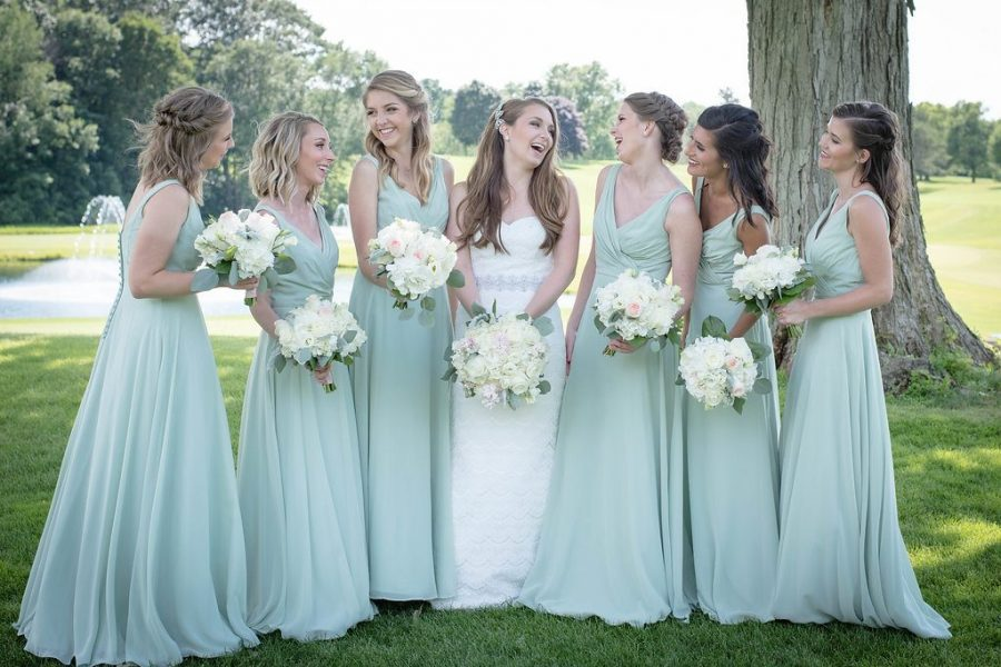 Bride and Bridesmaids in soft blue/green dresses on golf course grounds