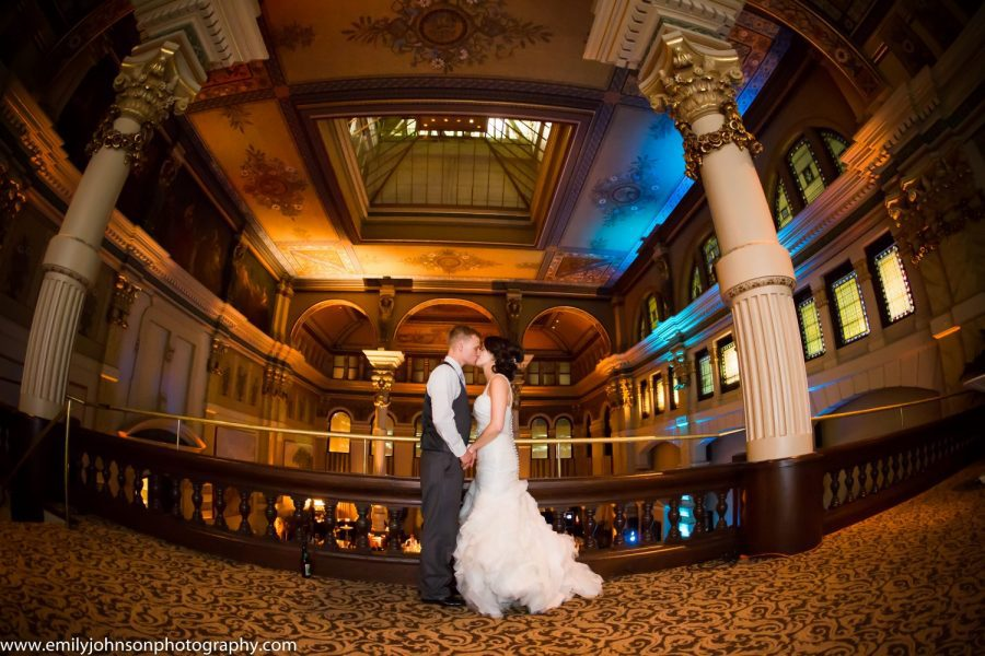 Bride and groom pose at the Grain Exchange Room in Milwaukee