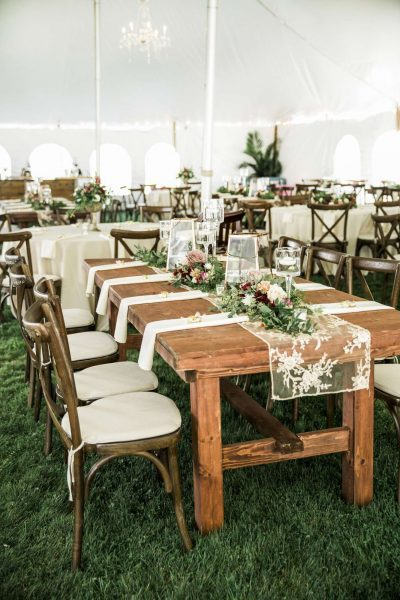Beautiful wood farm tables at a tented wedding- All Star Rentals