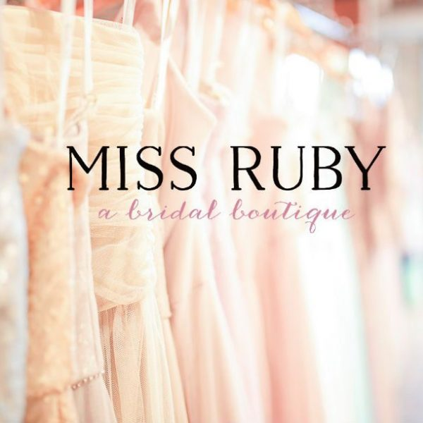 Dresses in background with Miss Ruby logo on top