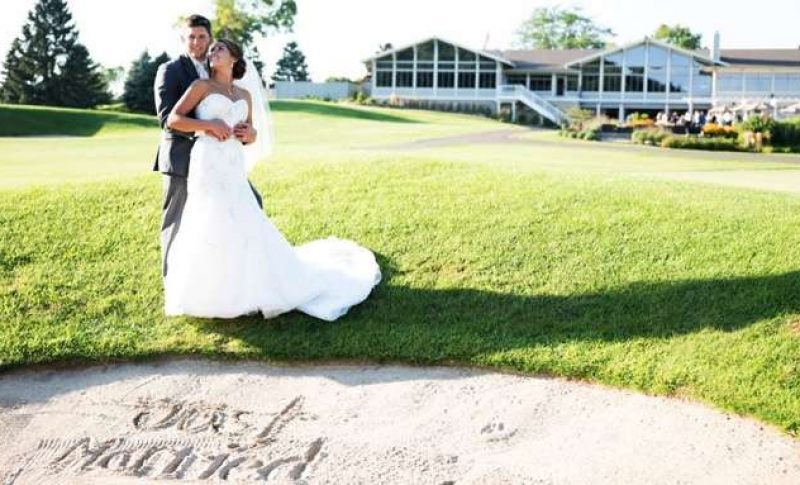Wedding couple standing on golf course with building in background