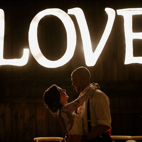 Couple dance with a lit up LOVE sign in background
