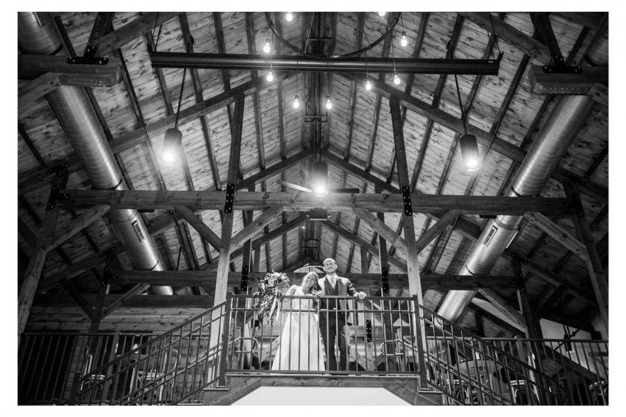 Bride and groom look out from loft