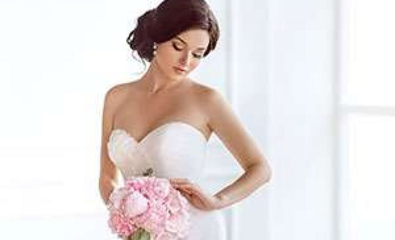 Strapless wedding gown with bride holding floral bouquet