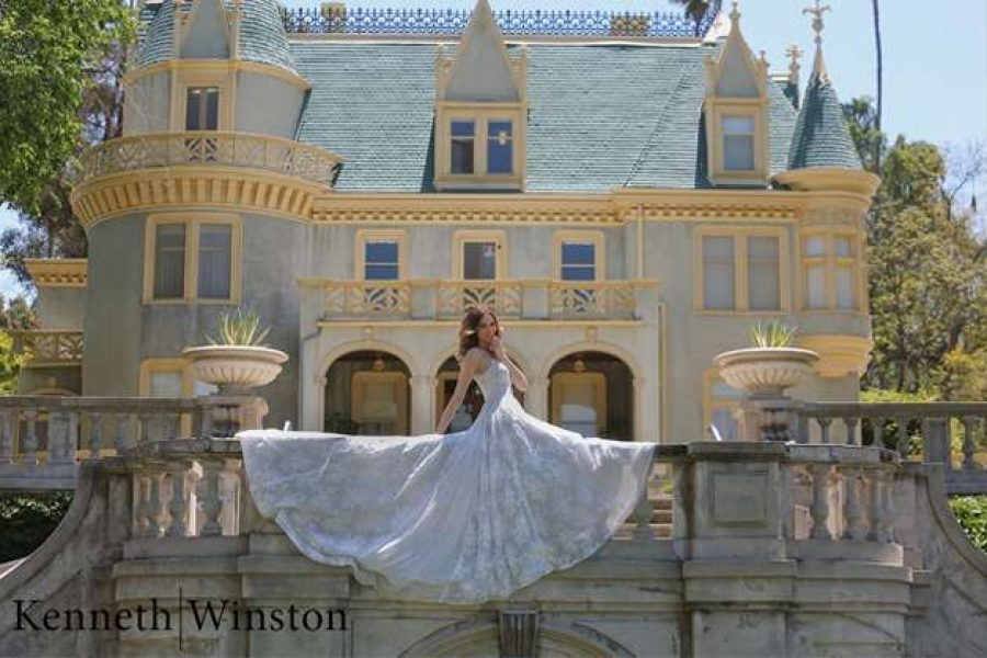 Stunning image of bride sitting on railing with Kenneth Winston Wedding Gown spread out