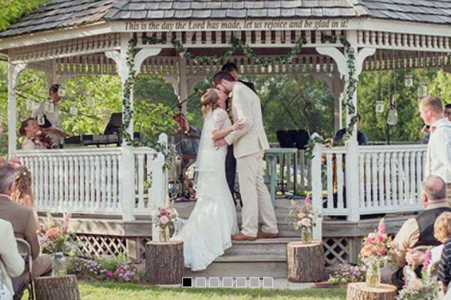 Wedding Couple Kissing under Gazebo at Lamms Gardens