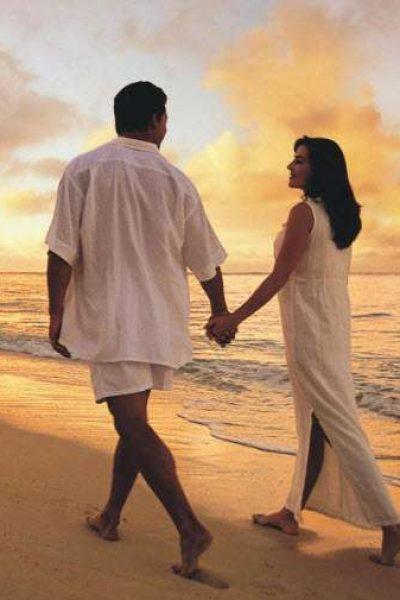 Honeymoon couple holding hands at warm destination