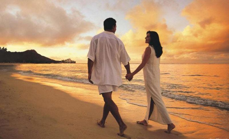 Honeymoon couple holding hands at warm destination