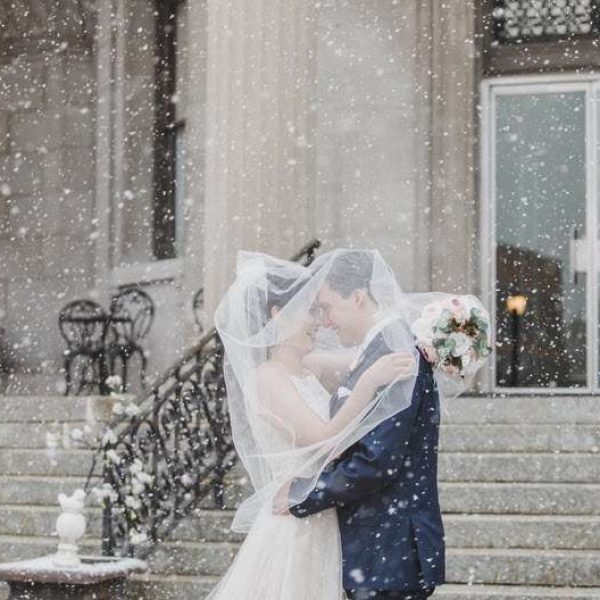Wedding couple in snowfall by Memorial Lane Photography
