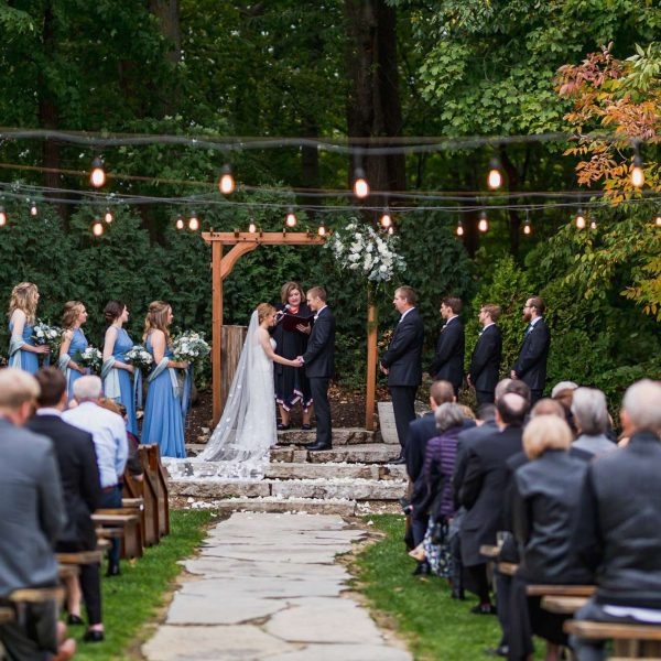 Bride and groom hold hands while saying vows | Wedding Venue- Terrace 167