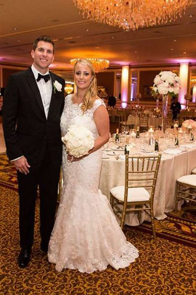 Wedding Couple in Grand Ballroom with fully decorated wedding reception showcased behind
