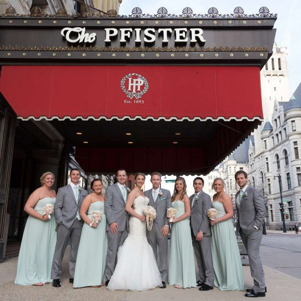 Wedding Party in Front of The Pfister Hotel. Dresses of light mint green and groomsmen in gray