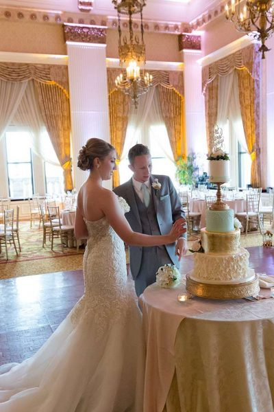 wedding couple cutting cake in Pfister Ballroom