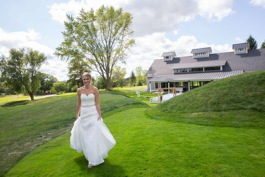 Bride walking on the gorunds in front of the Carriage House in Oconomowoc
