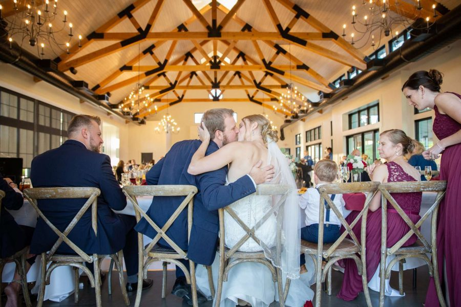 Bride and groom kiss at the head table. The Carriage House, a venue in Oconomowoc, WI