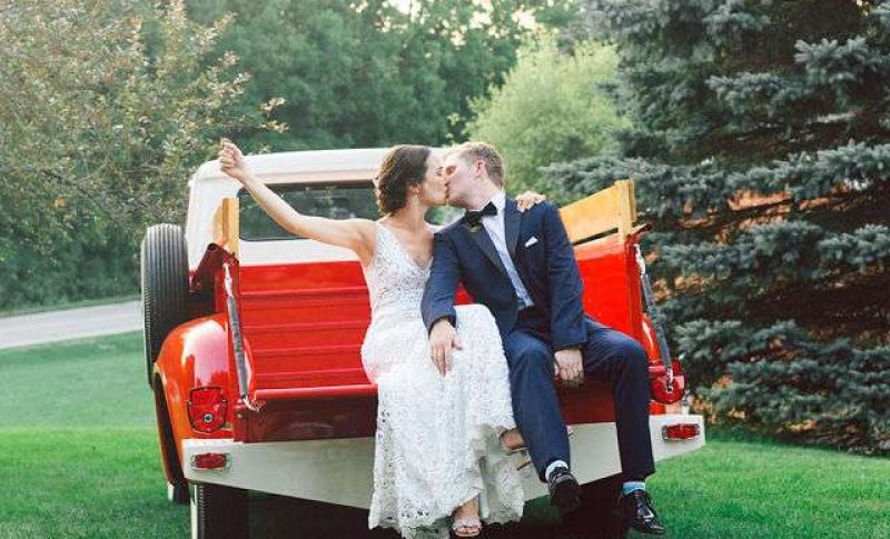 cute image of wedding couple kissing in back of truck with planning by evenement