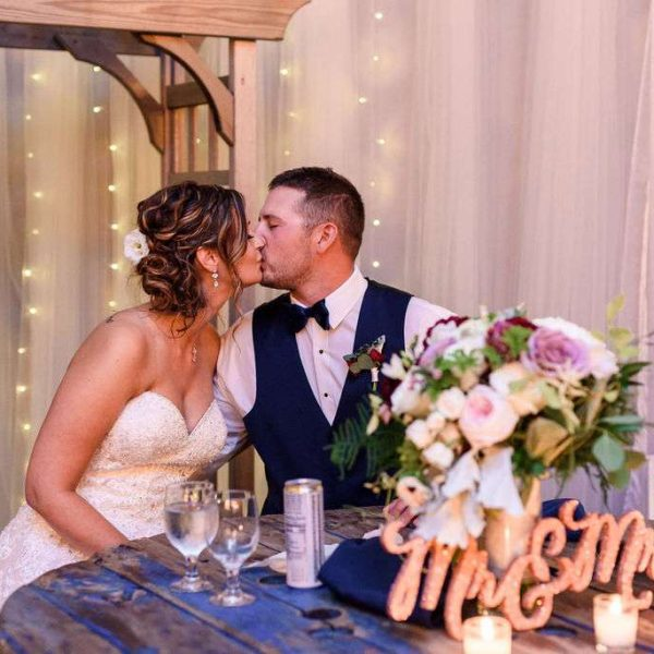 Wedding couple kiss at their sweetheart table