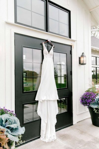 Wedding gown hung on front door of the Carriage House at Lac La Belle