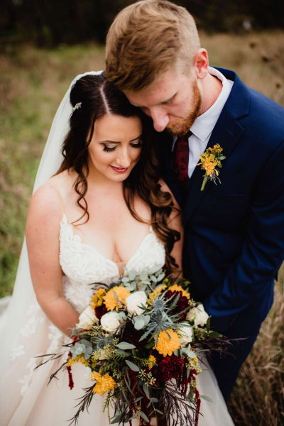 Bride and groom gaze down at her beautiful bouquet from Alfa Flower & Wedding Shop