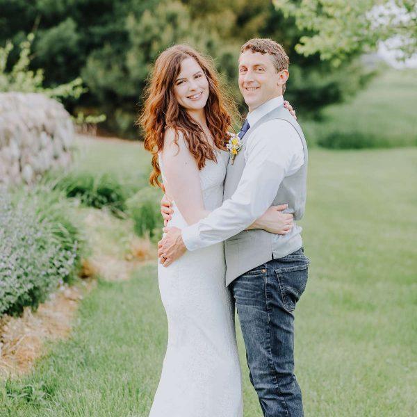 Bride and groom embrace in garden