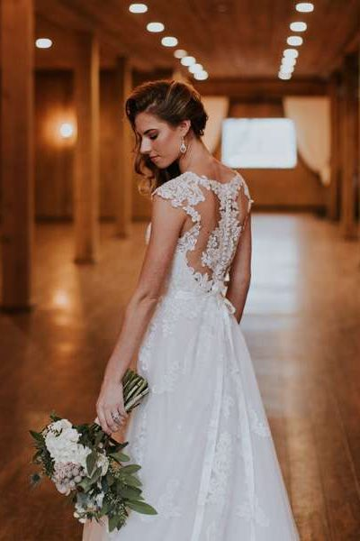 Side, back image of bride in her wedding gown, holding bridal bouquet down.