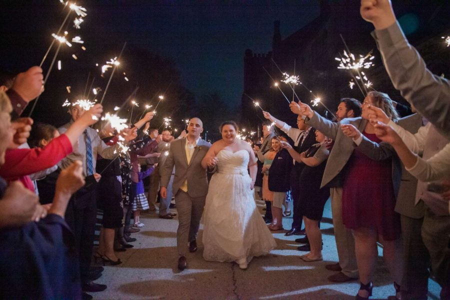 Bride and groom walk through tunnel of guests holding sparklers