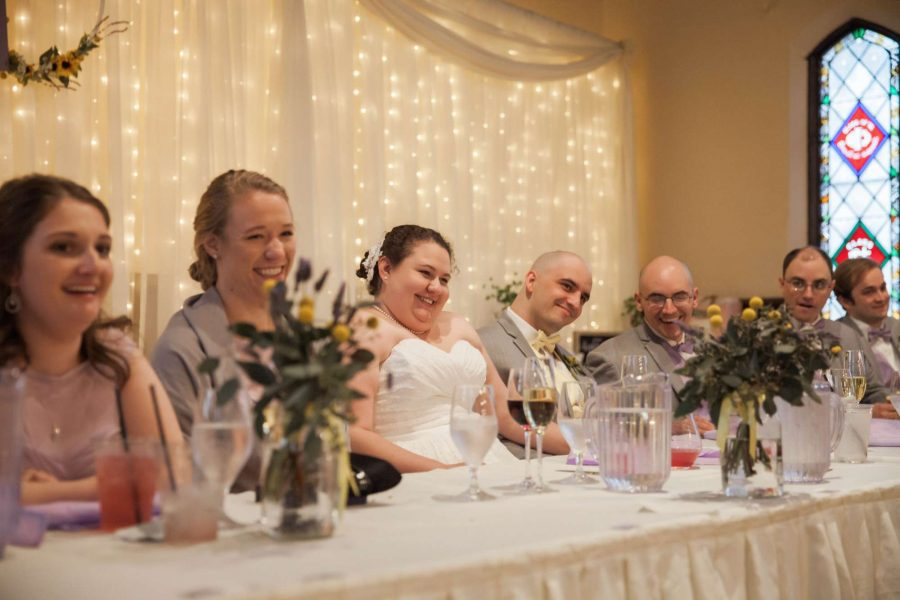 Bride and groom seated at the head table laugh