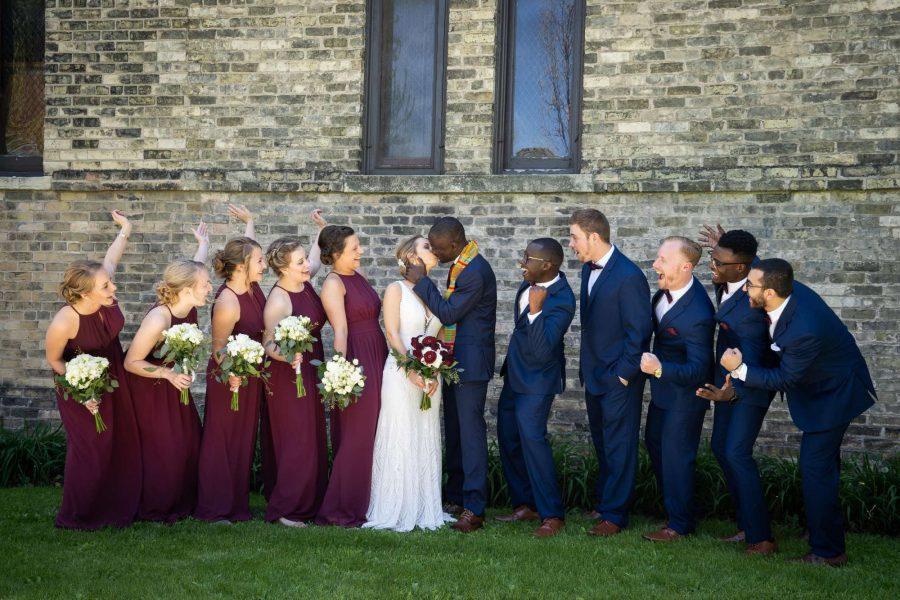 Groom kisses bride as wedding party looks on