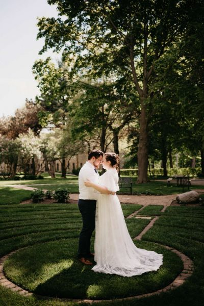 Bride and groom embrace on the ground of the Dekoven Center in Racine, WI