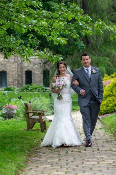 Wedding couple strill arm in arm down path at Dekoven Center