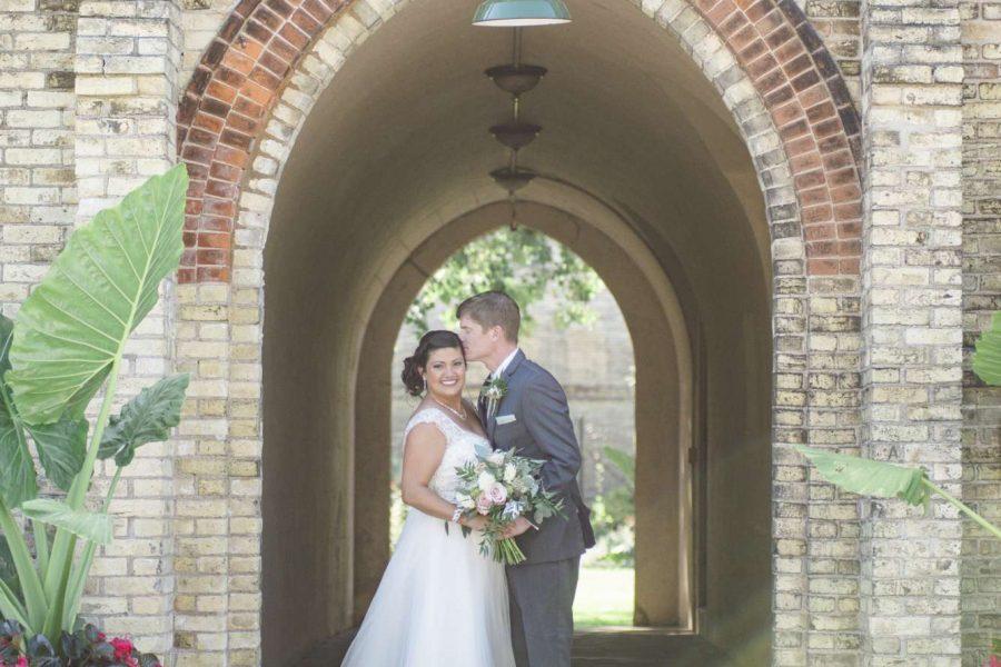 Wedding couple pose under brick arch