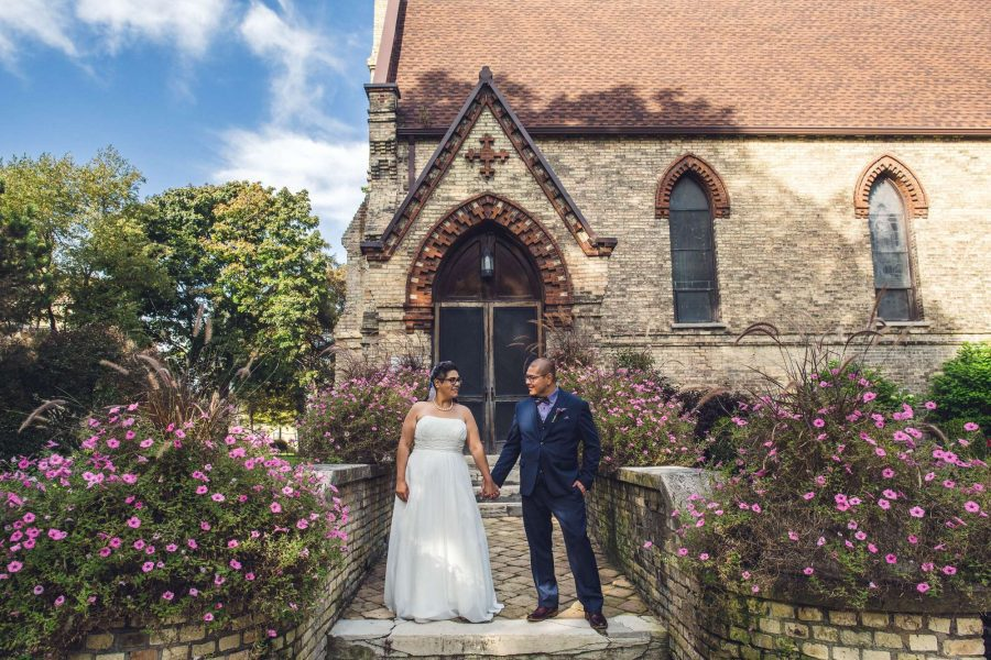 Bride and groom pose outside of St. John's Chapel