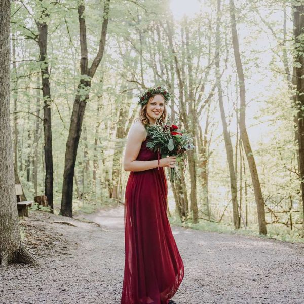 woman in red gown with bouquet and floral headpiece- Devils Lake